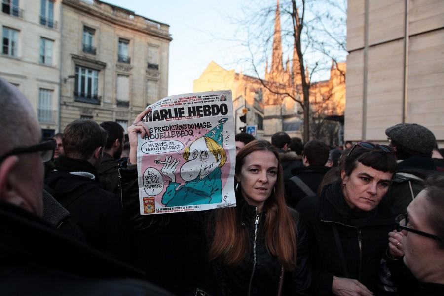 People hold up tributes to the victims of the Charlie Hebdo shooting on Jan. 7, 2015 during a 1-minute silence in Bordeaux, France, in remembrance of those killed and wounded in the deadly attack in Paris on Wednesday. Gunmen killed 12 people at the Paris office of French satirical magazine Charlie Hebdo in an apparent militant Islamist attack. Four of the magazine's well-known cartoonists, including its editor, were among those killed, as well as two police officers. A major police operation is under way to find three gunmen who fled by car.