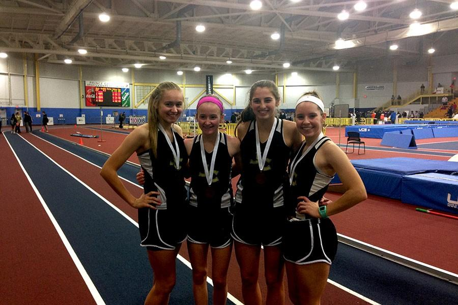 Junior Kristen Isoldi, sophomore Charlotte Haggerty, junior Holly Driver, and senior Nicole Clauter pose after winning the bronze in the varsity women's 4 by 400 race. The women's indoor track team won fifth place in the IAAM championship meet on Jan. 30.