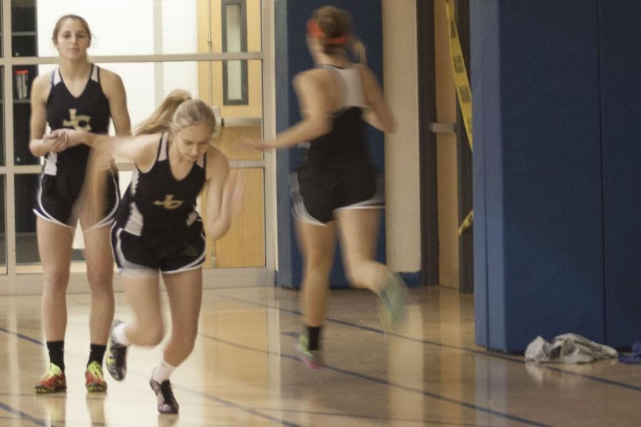 Junior Kristen Isoldi takes off into her leg of the 55 meter shuttle sprint as fellow junior Sam Carey finishes. The other two members of the record breaking team were junior Holly Driver and sophomore Charlotte Haggerty. The team scored a record overall time of 33.3 seconds.