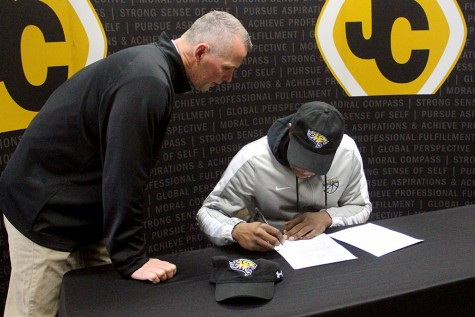 Head football coach Keith Rawlings directs senior Malik Tyne on where to sign his National Letter of Intent. Rawlings convinced Tyne to come out for football and Tyne played running back and outside linebacker.