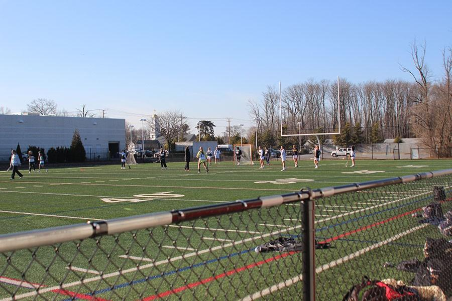 The women's varsity lacrosse team practices on Tucker Field in Hickory, MD. Women's varsity lacrosse has only three substitute players, while JV has no substitutes.