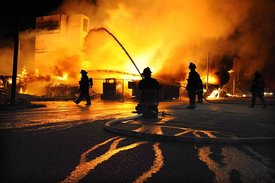 Baltimore firefighters battle a three-alarm fire at Gay and Chester Streets on Monday, April 27, 2015, in Baltimore. It was unclear whether it was related to ongoing riots. (Jerry Jackson/Baltimore Sun/TNS)