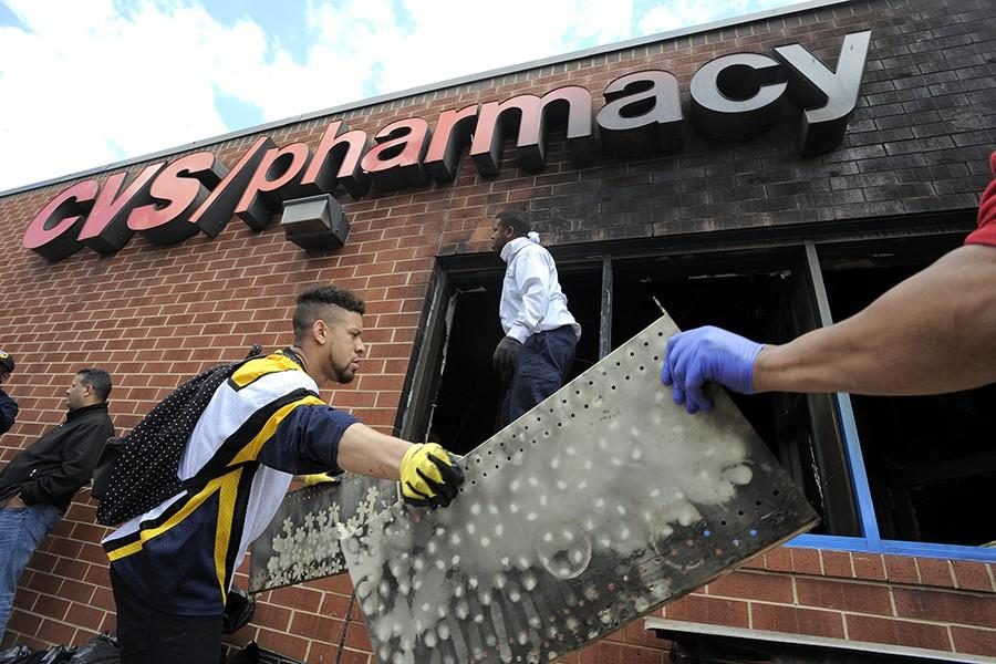 Volunteers work to help clear out debris from the CVS on North Avenue on Tuesday, April 28, 2015, in Baltimore. The store caught fire during Monday's riots. (Lloyd Fox/Baltimore Sun/TNS)