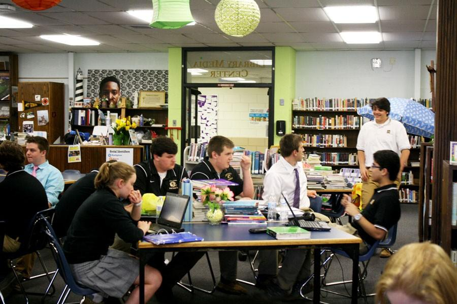 Students gather around a library table socializing. The library has become more of a social hangout spot than a place to work.