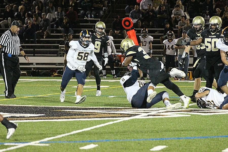 Junior+running+back+Devin+Darrington+charges+forward+over+the+body+of+the+St.+Paul%27s+player+with+the+ball.+Darrington+has+a+total+of+592+rushing+yards+this+season+and+seven+touchdowns.