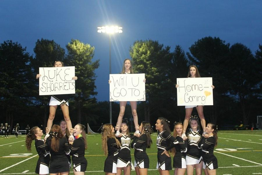 The junior and senior cheerleaders stand in formation at the first home football game under the new lights against St. Paul's. The team helped sophomore and patriot mascot Ashley Schwartz ask her date to homecoming. Cheerleaders are now limited to only sideline performances for football games after the decision to cut their competition routine.