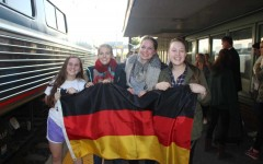Juniors Leah Monaghan and Katherine Grimm hold up the German flag with their exchange students Merle Rohde and Victoria Schiedeck. Monaghan and Grimm brought the flag with them to the train station to pick up their exchange students and welcome them to Bel Air.