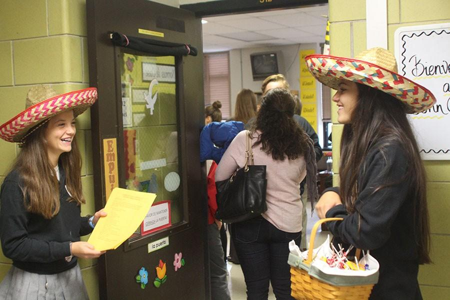 Sophomores Anna Sullivan and Kathryn Hodges wait outside of the Spanish classroom with candy to greet prospective students. The Open House on Oct. 17 included a student panel, a rocket launch attempt, a jazz concert, and student-led tours among other things.