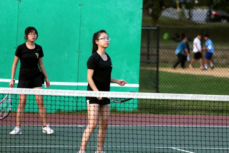 Seniors Vanilla Tong and Lucy Chen prepare for their opponent's serve during a tennis match at Pallotti. The varsity women's tennis team won the match against Pallotti 5-0.