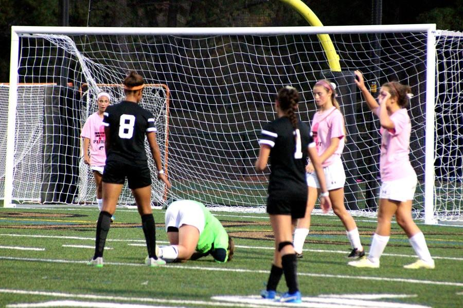 Junior goalie Nickie Stefanik lies on the ground, in pain, after an opposing player's foot collided with her head. Stefanik was immediately taken off the field and observed by trainers.