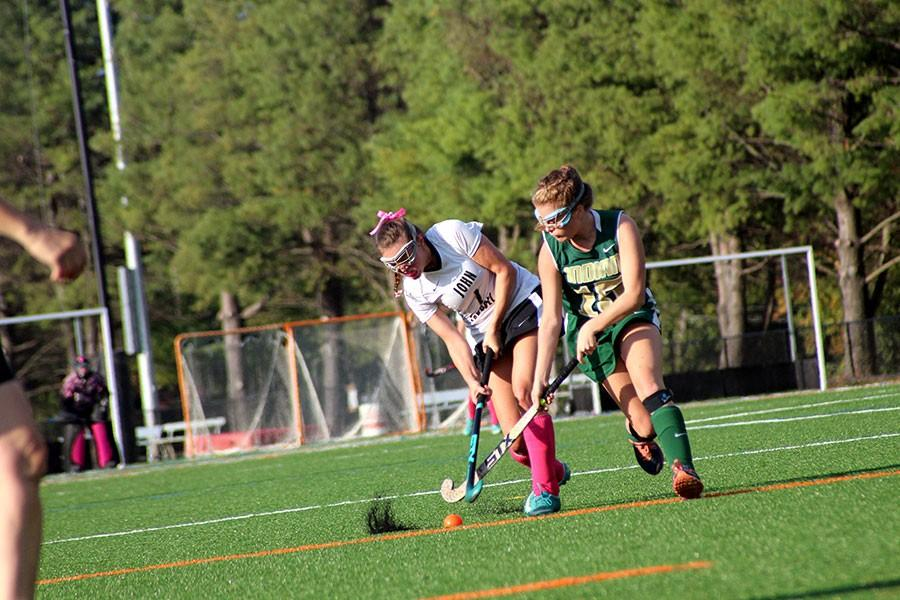 In the first half, senior varsity right midfielder Carly Lyon battles through an Indian Creek defender. The varsity field hockey team beat Indian Creek 4-3 in their breast cancer awareness game on Oct. 13.