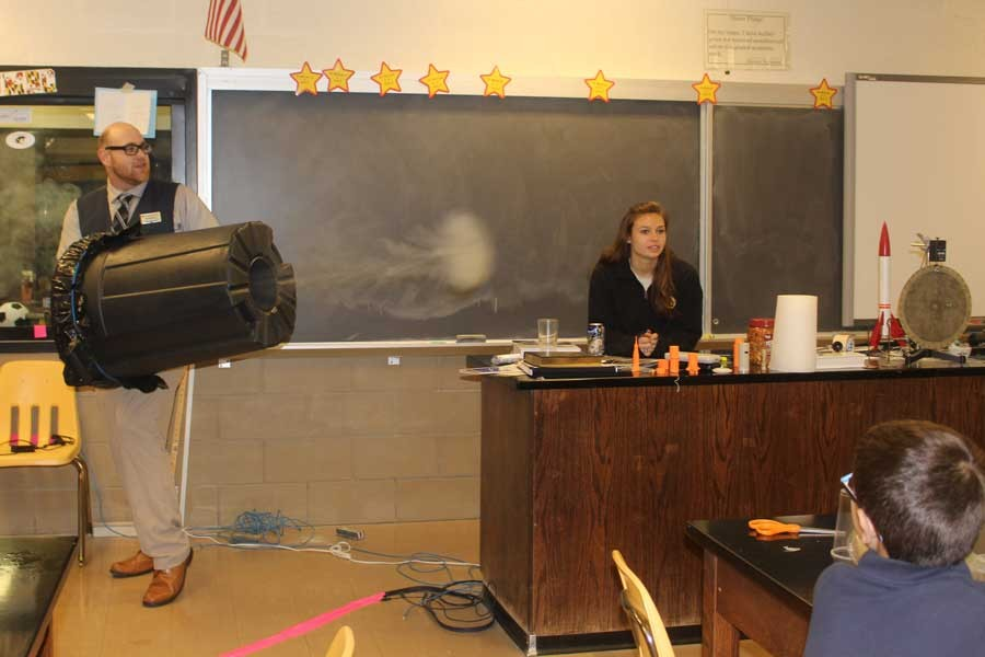 Physics teacher Anthony Davidson shoots off a vortex cannon in front of elementary and middle school students. Senior Carly Lyon aided Davidson during the night to help students make their own mini-cannons.