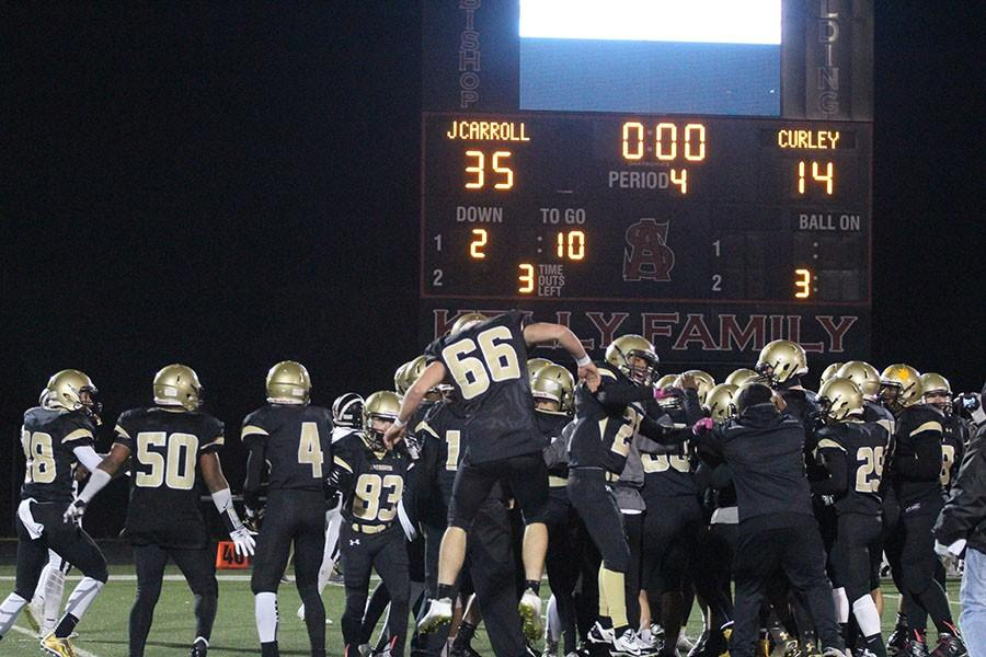 The varsity football team celebrates after their 35-14 win against Curley in the MIAA B conference championship. This marks the football team's first undefeated season in school history and first B conference championship since 2003.