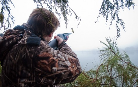 Tyler Thompson, class of '15, aims and fires off into the sky above an inlet in Cambridge, Maryland, hoping to hit a goose flying in the distance. Thompson often hunts waterfowl with family and friends including senior Michael Imbierowicz, who believes the key to hunting is