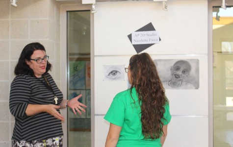 New substitute art teacher Erin Stellman offers advice to senior Nicolette Ficca about her AP Studio Art portfolio. Stellman currently teaches Introduction to Drawing and Studio classes.