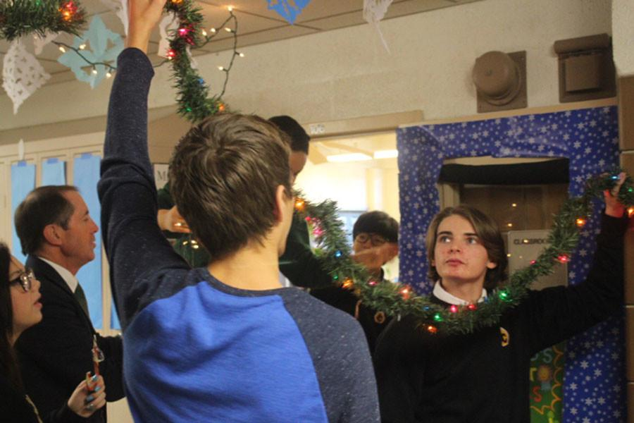 Hunter Peverley hangs decorations on the ceiling next to his advisory. The annual door decoration competition motivates students and faculty to put up extravagant hallway decorations.