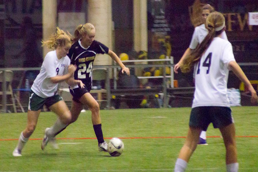 Senior center defenseman Kristen Isoldi dribbles the ball past a St. Paul's player in an indoor soccer game on Dec. 2, that ended in a 8-0 win for the Patriots. The team hopes to repeat their success and make it to the championship.