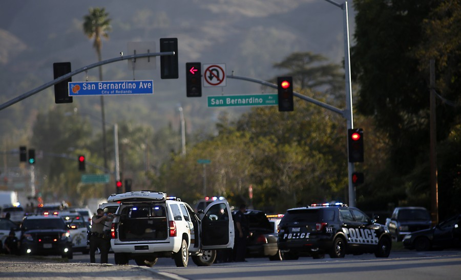 Law enforcement officers with guns drawn on San Bernardino Avenue in the pursuit of suspects in a mass shooting in San Bernardino, Calif., on Wednesday, Dec. 2, 2015. (Francine Orr/Los Angeles Times/TNS)