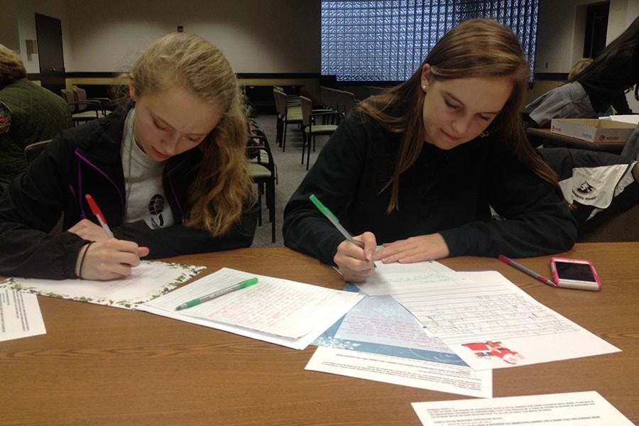 Juniors Erica Deyesu and Elaina Bonner write Christmas letters to students of St. Margaret's under the elf names
