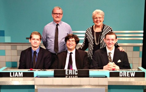 Senior Liam Dunn, Academic Team captain senior Eric Wright, and sophomore Drew Forthman (left to right) pose with academic team coach Robert Schick and Principal Madelyn Ball behind the Academic Team desk at the taping of