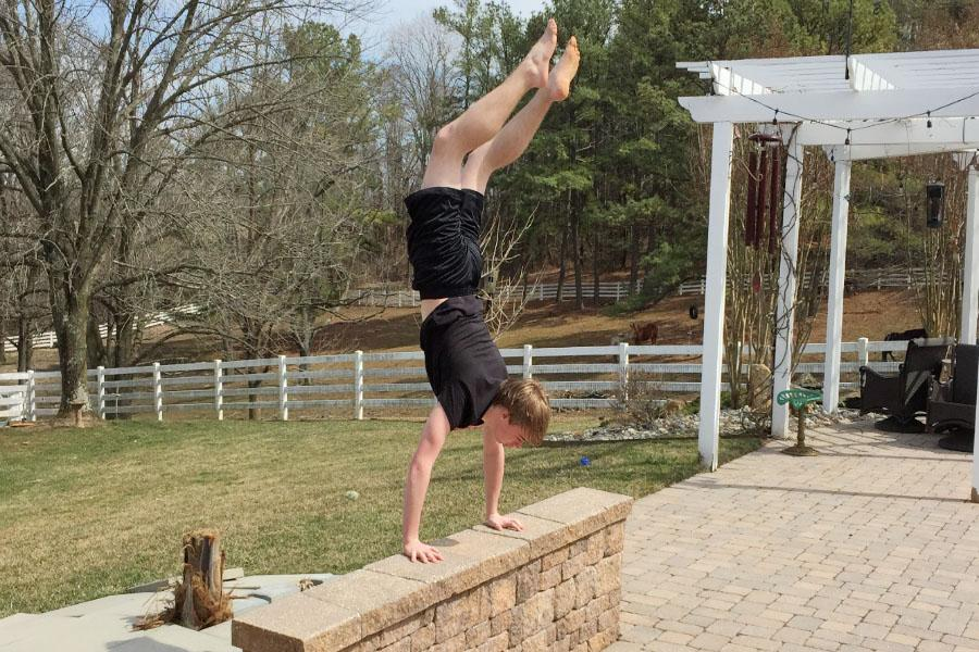 Holding himself up, sophomore Josh Pattisall does a handstand on a brick wall. Pattisall has been doing parkour and freerunning for the last two-and-a-half to three years.