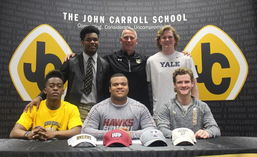 Seniors Josh Payne-White, Ky'el Hemby, Damon Lloyd, Kurt Rawlings, and Alex Rasmussen (left to right) officially ended the recruiting process with help of varsity football head coach Keith Rawlings (back center) after they sign their National Letters of Intent. During this signing period, seven student athletes committed to Division I and Division II colleges.