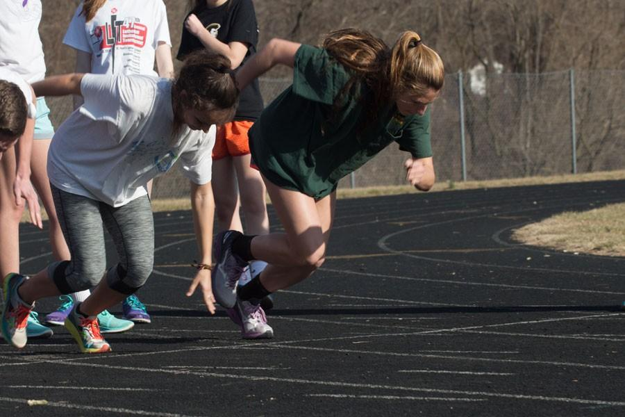Seniors Faith Ensor and Holly Driver sprint ahead inside their lanes during practice. Driver and Ensor are returning seniors and leaders on the women's track team.
