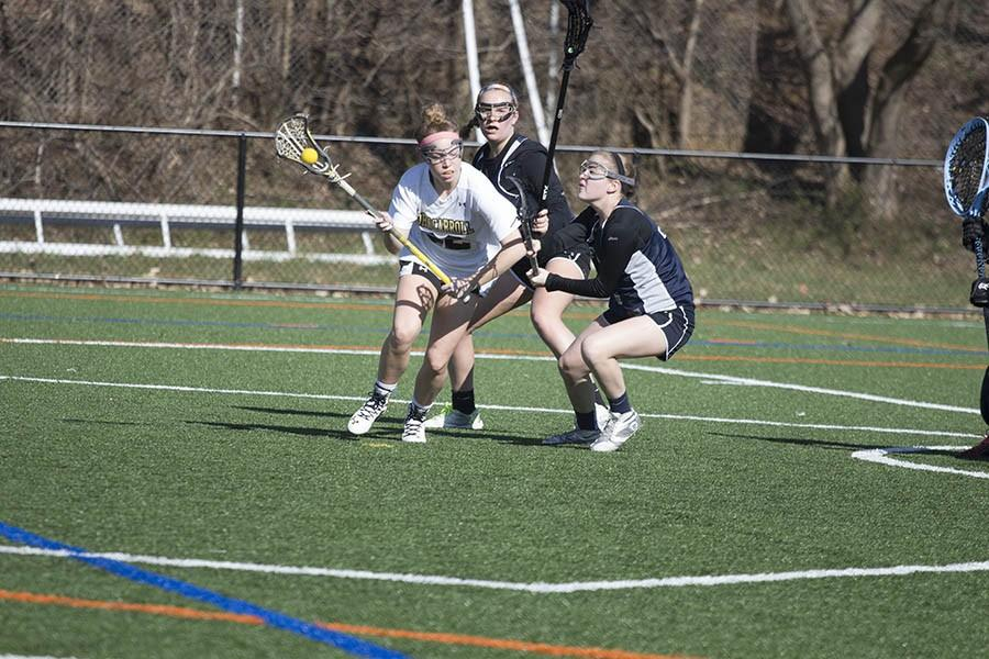 Senior varsity attack-man Mary Kate Gerety dodges two defenders during the women's varsity lacrosse game against the Peddie School. Gerety had five goals and four assists in the game to help win 21-6 on March 18.