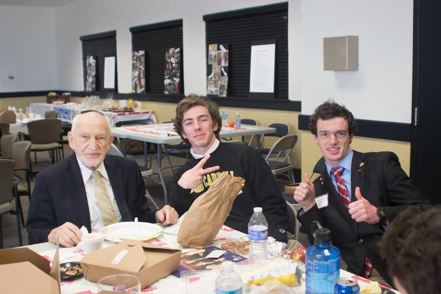 Seniors Matt Becker and Alex Kaufman pose with Holocaust survivor Werner Cohen during the lunch provided for the survivors and their hosts. Senior hosts spent the entire day with one survivor in order to get to know them better.