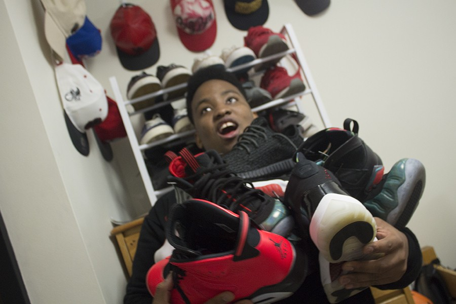 Senior Ben Flomo holds his shoe collection worth thousands of dollars in his arms. Flomo's newest addition is a pair of Yeezys, Kanye West's shoe line, which have been reported to sell for $3,500.