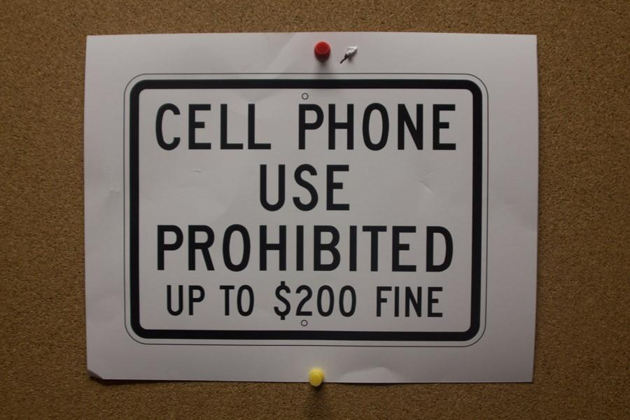 Signs in the hallways jokingly reference the new phone policy. Cell phone usage is now prohibited in the academic wing but allowed in the non-academic areas of the school.