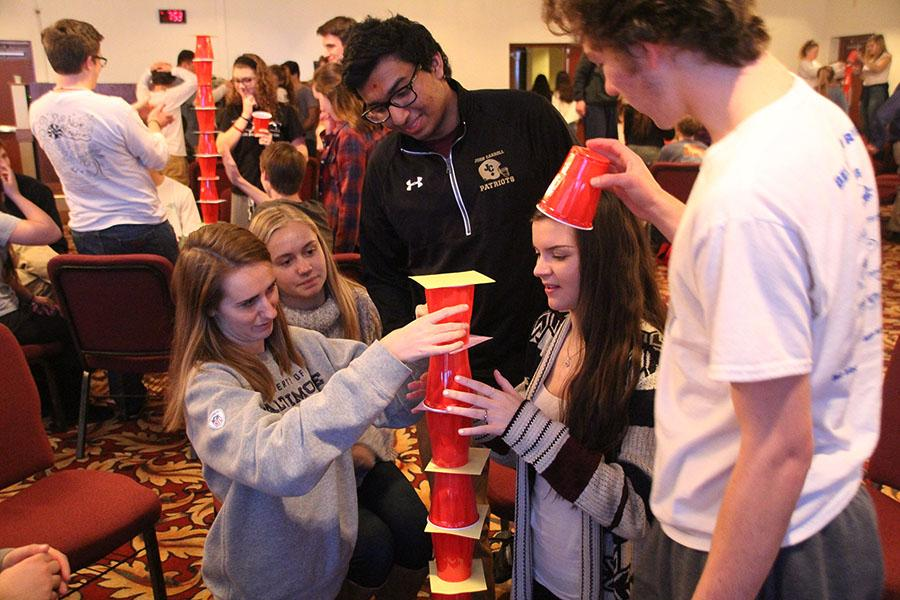 Seniors Cara Wolfarth, Kristen Isoldi, Kishan Patel, Jessica Fuchsluger, and Matthew Becker (left to right) bond over a tower-building challenge at retreat.