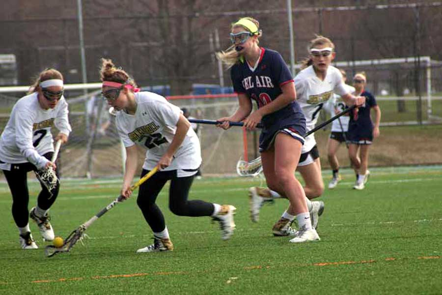 Varsity women's lacrosse players senior Mary Kate Gerety and sophomore Molly Lynch pounce on a loose ball. The team played Bel Air High School on March 21 and won in overtime 10-9.