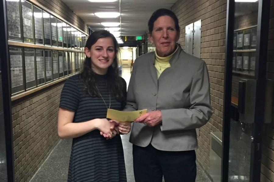 French teacher Regina Ferry hands Junior Erin McCaughey the annual Laura Pelligrini French Award for showing excellence and enthusiasm in the study of the French language. The award was given at the annual World Languages Honor Society Inductions on April 7.