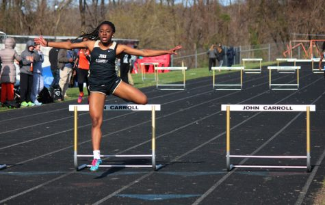 Sophomore Chika Chuku jumps over a hurdle during a race. The women's track team finished with a record of 9-3 and came fourth in the championship.
