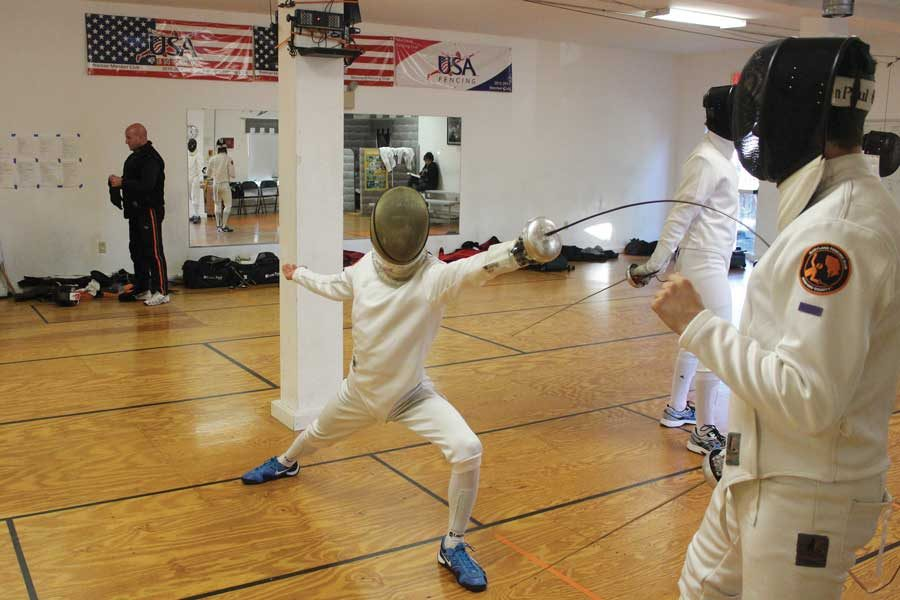 Freshman+fencer+Jack+Plumer+lunges+forward+with+his+epee.+Plumer+has+been+fencing+competitively+for+four+years.