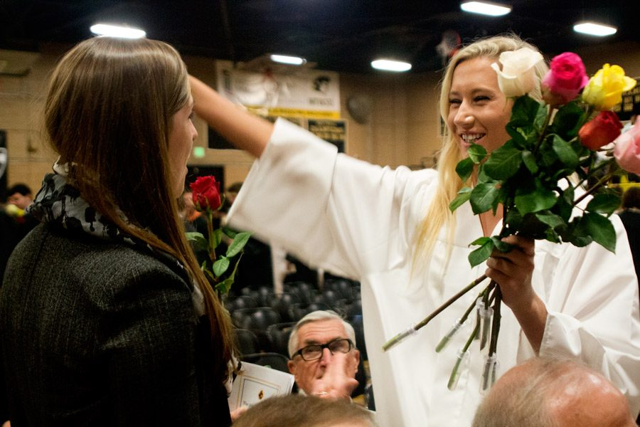 Senior Alex Dippel leans in to hug English teacher Hayley Howe after giving her a letter and rose during the Baccalaureate Mass. As part of the graduation tradition, seniors write letters to the people who have helped them during the past four years and hand them out during the Baccalaureate Mass.