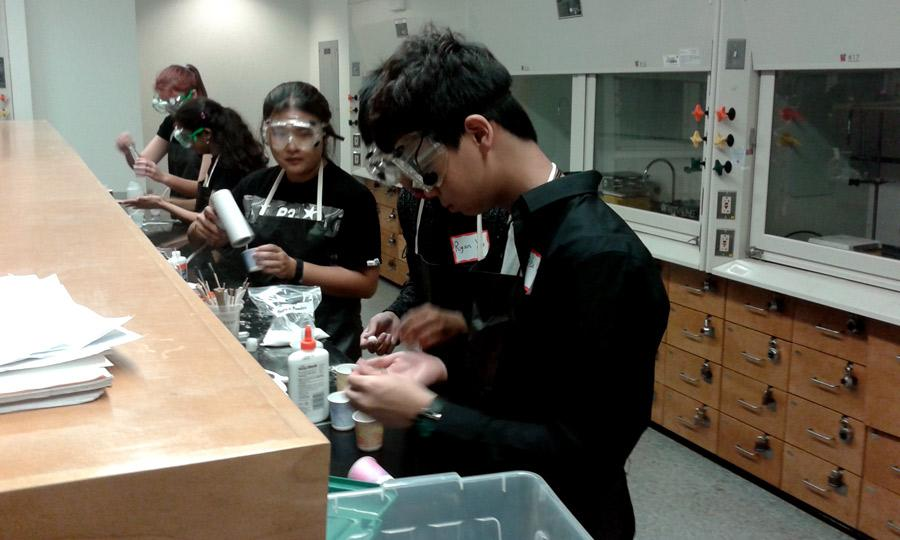 Level 1 sophomores Suky Pei, Ryan Xu, and Alex Yuan (left to right) work on a lab experiment called Viscoelastic Bounce, where they made bouncy balls out of glue. The Level I team placed second for their bouncy ball.