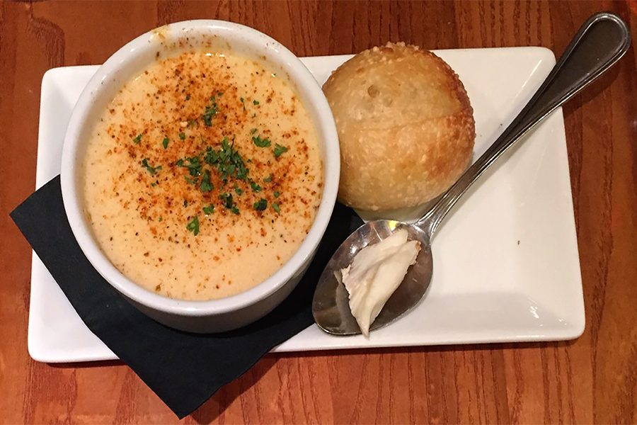 Pairings Bistro has many popular appetizers like this  cup of cream of crab soup with a dinner roll on the side.