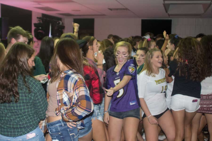 Juniors Katie Mills (left) and Mackenzie Lawry (right) dance with their friends during the Back to School Dance on Sep. 9. The Back to School Dance is held annually in order to encourage students to get excited about the upcoming school year.