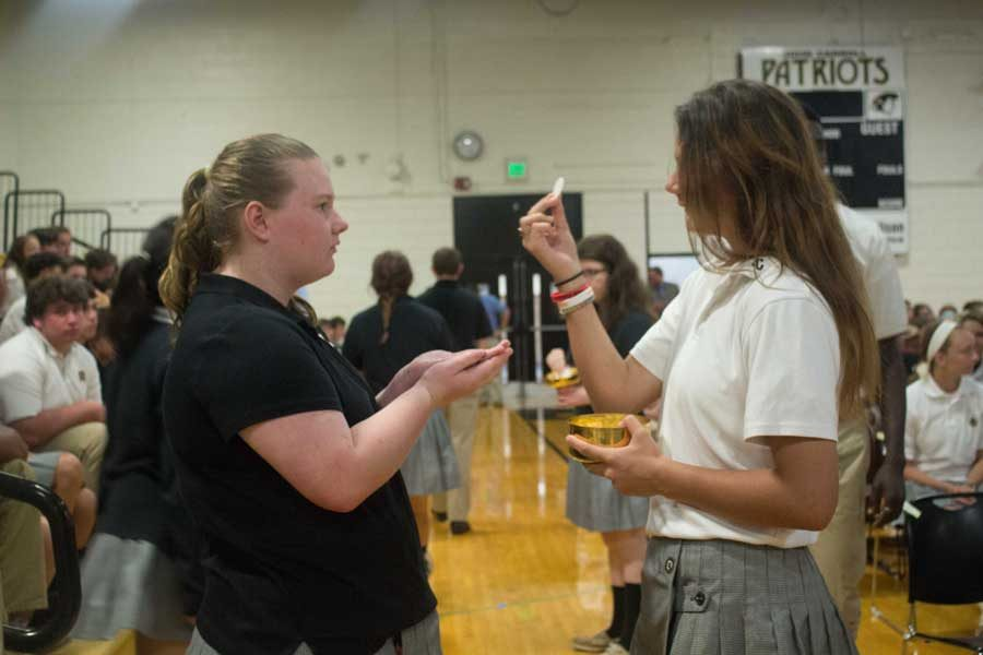 Sophomore Emma Olsen receives Communion from senior Sarah Meyerl during the opening mass on Thursday, Sept. 8. Each year, JC holds an opening mass to celebrate the beginning of the school year.
