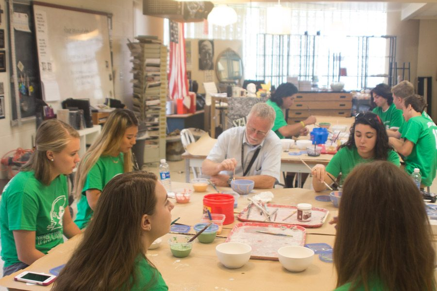 Math teacher Andrew McIntyre and a group of senior girls paint bowls as a part of a service station. The bowls will be given to those who attend Empty Bowls, an event run by St. Vincent de Paul of Baltimore that raises money to serve the hungry and homeless in the community.
