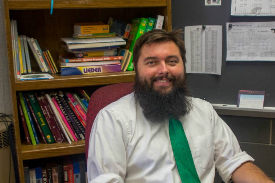 German teacher Mark Canter poses for a picture at his desk. The Patriot randomly chose 15 new members of the community to find out why they chose JC and their expectations.