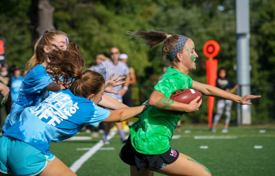 Senior Charlotte Haggerty runs down the field as she is chased by two juniors during the 2016 Powderpuff Game. The senior class won the game 18-12 with a touchdown in the last minute of the game.