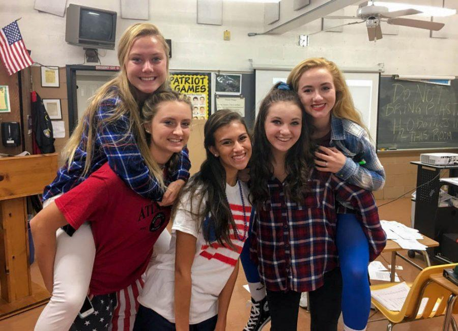 Freshman Kaitlyn Sydnor, seniors Eryn Roach and Hailey Ishak, sophomore Rachel Miller, and junior Katie Mills (left to right) pose during advisory while wearing red, white, and blue on Nationality Day during Spirit Week. Students were able to wear their countrys respective colors to represent their nationality on Tuesday.