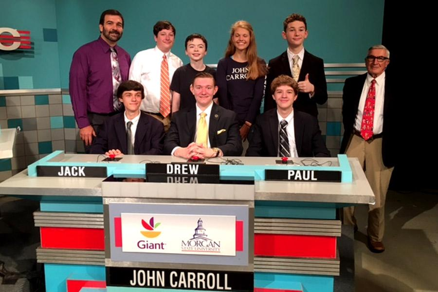 Sophomore Jack Plumer, Academic Team captain junior Drew Forthman, and sophomore Paul Capobianco (left to right) pose with the Academic Team moderator Chris Deaver, sophomores Pierce Berger and Ryan Newberry, freshmen Alexis Loder and Leo Hojnowski, and former Russian teacher Edward Miller (left to right back row) at the taping of