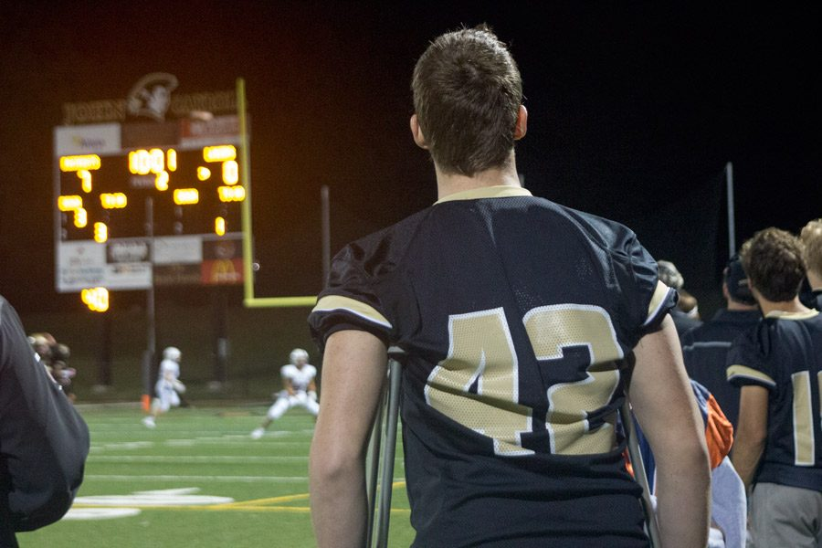 Senior Michael Cooper watches the Homecoming Game against Boys' Latin from the sidelines. Ever since Cooper broke his femur during the football game against Calvert Hall on Sept. 2, he has been out for the season and has attended class via Skype.