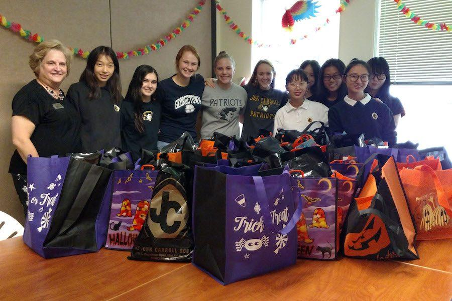 Service club moderator Susan Strawbridge and members (left to right) Christina Zhang, Katie Yurechko, Olivia Collins, Emily Smith, Caitlyn Trent,  Iriski Hu,  Lily Chen,  Christina He,  Jocelyn Hu, and Yue Yue Xiong stand together with the bags they made for the families at the Ronald McDonald House in Baltimore. Students took a field trip there on Wednesday, Oct. 19 after the PSAT to deliver the bags.