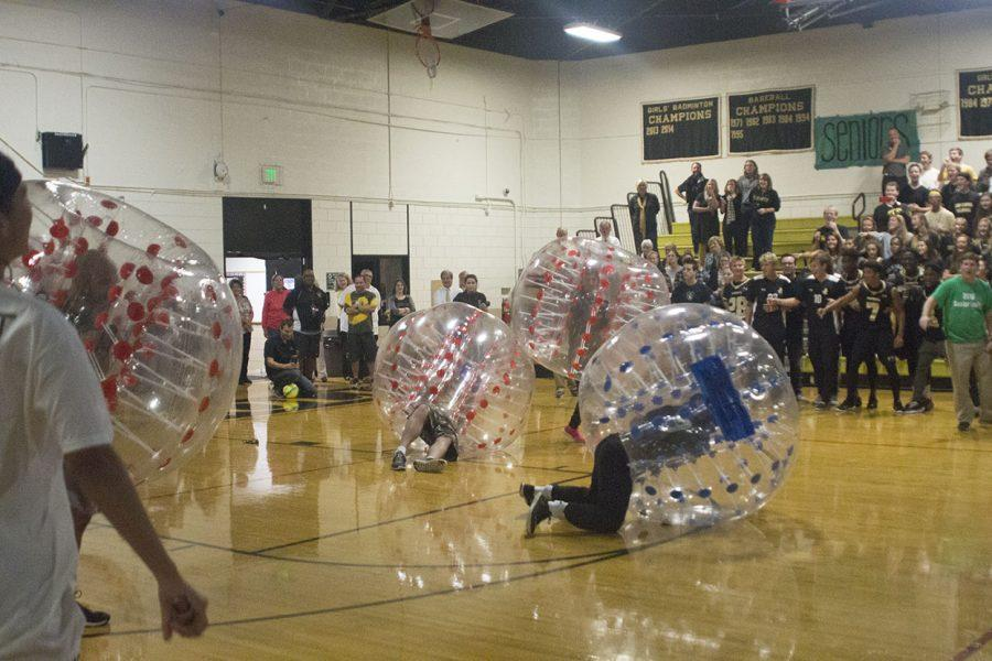 Students cheer as physics teacher Anthony Davidson is knocked to the ground during a game of bubble-soccer at the Spirit Week pep rally. The pep rally took place Friday, Oct. 7 in the Upper Gym.