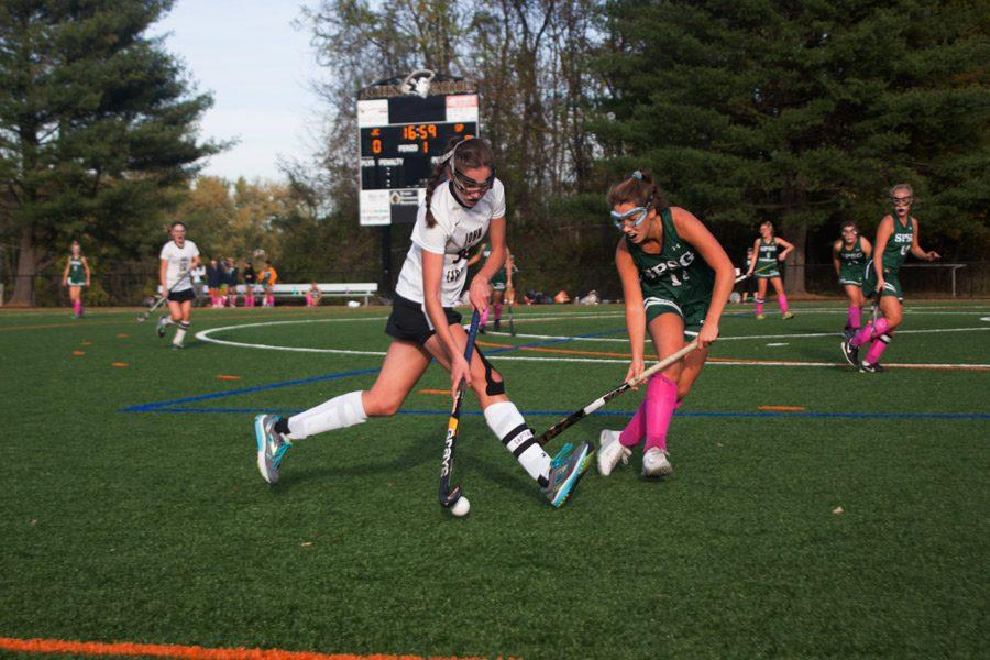Senior right midfielder Emily Stancliff shields the ball from a defender while carrying it down the field. The varsity field hockey team beat St. Paul's 2-0 on Oct. 31 to advance to the semifinals.